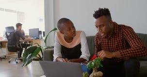 Вид спереди молодого черных планирования и сидеть команды дела на кресле в офисе 4k сток-видео
