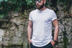 Вид спереди Молодой бородатый тысячелетний человек одетый в белых футболке и солнечных очках стойки против темной стены Насмешка  стоковые фото