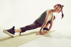 Вид спереди молодой женщины протягивая тело в классе гимнастики Стоковое Изображение