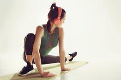 Вид спереди молодой женщины протягивая тело в классе гимнастики Стоковые Изображения