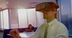 Вид спереди молодой кавказской мужской исполнительной власти используя шлемофон виртуальной реальности в современном офисе 4k видеоматериал