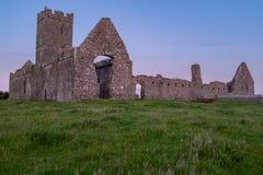 Вид спереди низкого угла руин аббатства Клары Augustinian снаружи Ennis монастыря как раз, графство Клара, Ирландия на заходе сол стоковые фото