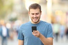 Вид спереди парня проверяя умный телефон снаружи Стоковые Фотографии RF