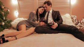 Вид спереди пар в любов кладя на кровать и выпивая вино для замедленного движения годовщины их Нового Года сток-видео