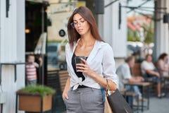 Вид спереди стильного студента идя в кофе центра города выпивая стоковые изображения