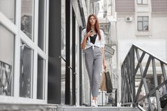 Вид спереди стильной одетой девушки идя вне магазина на улице стоковая фотография