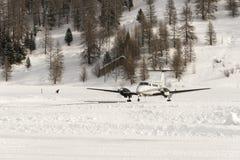 Вид спереди частного самолета готового для того чтобы принять в снег покрыло ландшафт и горы в горных вершинах Швейцарии в зиме Стоковая Фотография