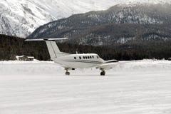 Вид спереди частного самолета готового для того чтобы принять в снег покрыло ландшафт и горы в горных вершинах Швейцарии в зиме Стоковое фото RF