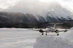 Вид спереди частного самолета готового для того чтобы принять в снег покрыло ландшафт и горы в горных вершинах Швейцарии в зиме Стоковые Фото