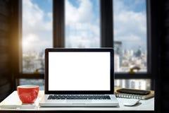 Вид спереди чашки и компьтер-книжки на таблице стоковые изображения rf