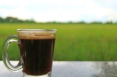 Вид спереди чашки кофе утра на открытой террасе против живых зеленых рисовых полей Стоковая Фотография