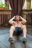 Вид спереди человека делая подбрюшные тренировки на поле дома стоковые фотографии rf