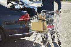 Вид спереди человека с магазинной тележкаой за автомобилем с раскрытым хоботом вне супермаркета стоковые изображения rf