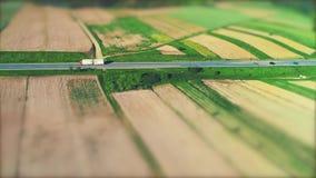 Вид с воздуха автомобилей, двигая дальше дорогу асфальта через изумляя ландшафт с плодовитыми полями 4K