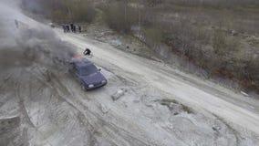 Вид с воздуха автомобиля быть горящий в дезертированных полях пыли с двигая мотоциклами сток-видео