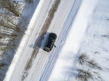 Вид с воздуха автомобиля на дороге зимы Сельская местность ландшафта зимы Воздушное фотографирование снежного леса с автомобилем  Стоковое фото RF