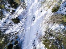 Вид с воздуха автомобиля на дороге зимы Сельская местность ландшафта зимы Воздушное фотографирование снежного леса с автомобилем  Стоковое Изображение
