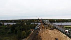 Вид с воздуха большого района конструкции с 2 кранами близрасположенными проезжей частью и полем видеоматериал