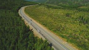 Вид с воздуха велосипедистов и автомобилей дороги Красный Транс-сибиряк весьма 4k Bull акции видеоматериалы