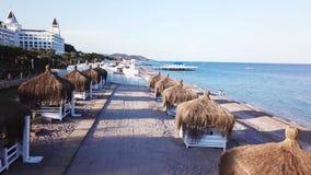 Вид с воздуха волн, песчаный пляж с камышовыми зонтиками видео Взгляд сверху песчаного пляжа с естественными umbrelas стоковые изображения