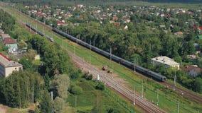 Вид с воздуха: Высокоскоростной пассажирский поезд вытягивает до станции в маленьком городе Россия сентябрь 2018 акции видеоматериалы