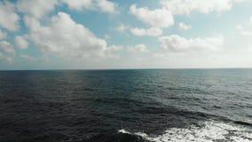 Вид с воздуха горизонта моря океана с голубым небом и облаками Сильные волны ударяя скалистый пляж создавая пену и брызгать акции видеоматериалы
