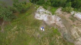 Вид с воздуха 3 девушек в длинных платьях лета кладя на высокий холм на реке Соединение с природой видеоматериал
