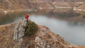 Вид с воздуха девушки сидит вниз на утесе на береге озера Видео перемещения видеоматериал