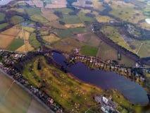 Вид с воздуха домов построил вокруг озера и поля для гольфа окруженных сельской местностью в Чешире Англии Стоковое Изображение RF