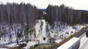 Вид с воздуха как автомобиль на дороге леса входит в тоннель и выходит он сток-видео