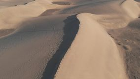 Вид с воздуха - красивая девушка стоя на дюне на заходе солнца или восходе солнца Трутень летая на высокой скорости над пустыней  видеоматериал