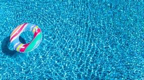 Вид с воздуха красочной раздувной игрушки донута кольца в воде бассейна сверху, концепция семейного отдыха Стоковые Фотографии RF