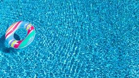 Вид с воздуха красочной раздувной игрушки донута кольца в воде бассейна сверху, курорт семейного отдыха Стоковые Изображения RF