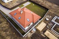 Вид с воздуха крыши нового дома с окнами и строительной площадкой чердака, учреждения будущего дома, стогов кирпичей и здания стоковые изображения rf