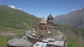 Вид с воздуха к церков троицы Gergeti около деревни Gergeti в Georgia, под держателем Kazbegi видеоматериал