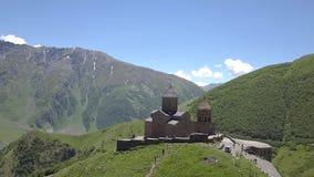 Вид с воздуха к церков троицы Gergeti около деревни Gergeti в Georgia, под держателем Kazbegi акции видеоматериалы