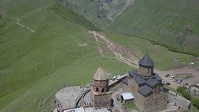 Вид с воздуха к церков троицы Gergeti около деревни Gergeti в Georgia, под держателем Kazbegi сток-видео