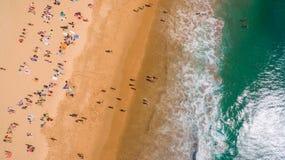 Вид с воздуха людей отдыхая на красивом пляже около океана, Португалии Стоковые Фото