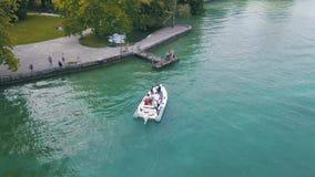 Вид с воздуха людей плавая на небольшую белую моторку около зеленого парка E Курорт лета видеоматериал
