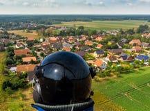 Вид с воздуха малой деревни в расстоянии за частью леса и спаржа field покрытый при фольга, сделанная с трутнем стоковые изображения