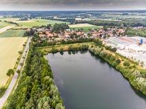 Вид с воздуха малой немецкой деревни за искусственным озером, которое было создано минированием песка для конкретного завода стоковое изображение rf