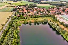 Вид с воздуха малой немецкой деревни за искусственным озером, которое было создано минированием песка для конкретного завода стоковая фотография