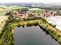 Вид с воздуха малой немецкой деревни за искусственным озером, которое было создано минированием песка для конкретного завода стоковые фото