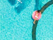 Вид с воздуха молодого плавания женщины брюнета на раздувном большом донуте с ноутбуком в прозрачном бассейне бирюзы стоковая фотография rf