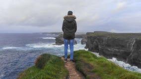 Вид с воздуха над положением девушки на скалах ирландского западного побережья стоковое фото