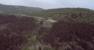 Вид с воздуха над curvy дорогами асфальта с автомобилями в горах акции видеоматериалы