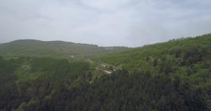 Вид с воздуха над curvy дорогами асфальта с автомобилями в горах видеоматериал