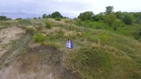 Вид с воздуха на 3 девушках нося длинное платье моды лета идя около озера или реки 2 кавказское и одно акции видеоматериалы