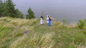 Вид с воздуха на девушках потехи танцуя нося длинное платье моды лета идя около озера или реки 2 кавказское и видеоматериал
