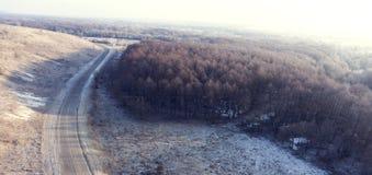 Вид с воздуха на дороге и ландшафт леса в зиме приправляют Стоковые Изображения